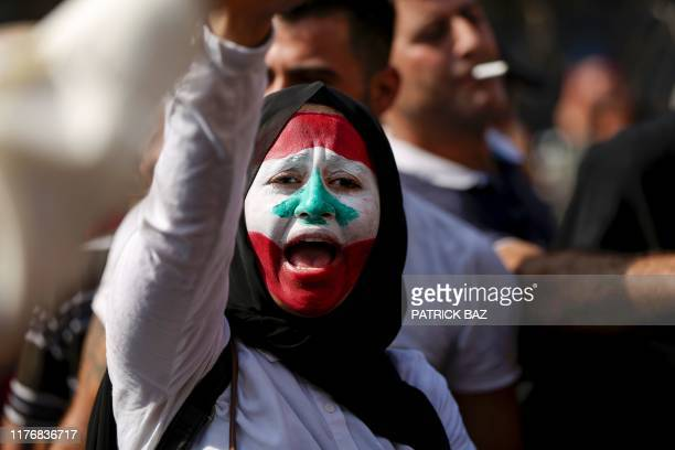 A Lebanese woman her face decorated with the national flag chants slogans during a protest at Riad alSolh Square in Beirut on October 19 2019 as...