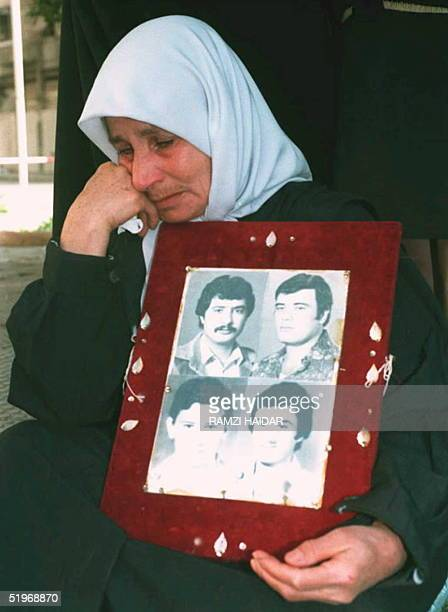 Lebanese woman holding portraits of her four sons abducted during the 19751990 Lebanese civil war cries after Lebanese House Speaker Nabih Berri...