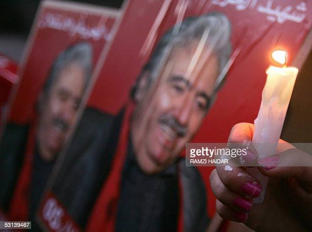 Lebanese woman holds a candle in front of a poster of slain former Communist party leader George Hawi during a gathering at the site where antiSyrian...