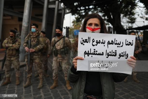 Lebanese woman holds a placard in front of soldiers during a protest against the country's political paralysis and deep economic crisis in Beirut on...