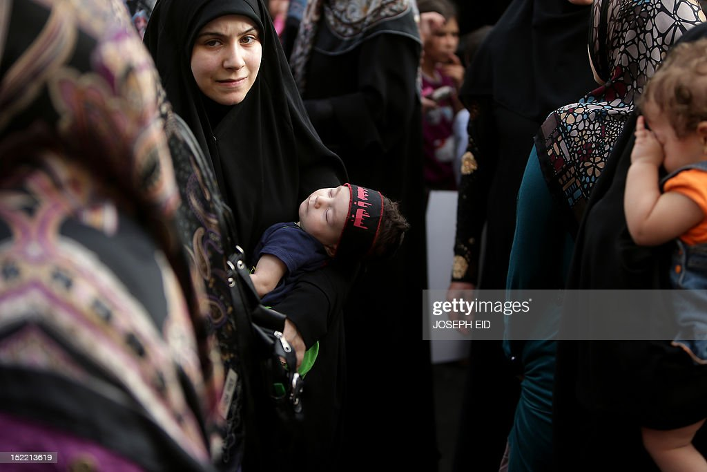 A Lebanese woman holds her sleeping child as supporters of Lebanon's Hezbollah take part in a rally in southern Beirut to denounce a film mocking Islam on September 17, 2012. Hezbollah chief Hassan Nasrallah, who made a rare public appearance at the rally, has called for a week of protests across the country over the low-budget, US-made film, describing it as the 'worst attack ever on Islam.'