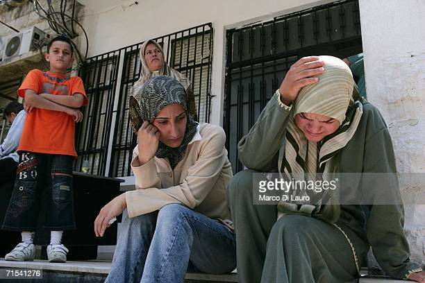 Lebanese woman look on at rescue teams wrapping bodies of the victims of the Qana's Israeli air strike in plastic at the morgue July 30 2006 in Tyre...
