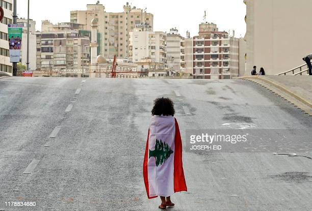 Lebanese woman protester walks draped in a national flag along the Fuad Chehab avenue near the Martyrs' Square in the centre of the capital Beirut on...