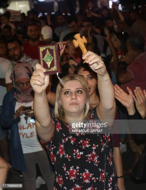 Lebanese woman raises a cross and a Koran during a protest against dire economic conditions in the Lebanese southern port city of Sidon , on October...