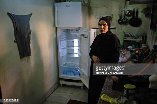 Lebanese woman stands next to her empty refrigerator in her apartment in the port city of Tripoli north of Beirut on June 17, 2020. - Lebanon's...