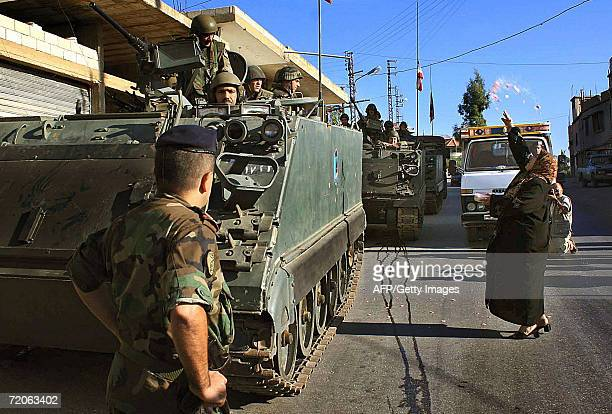Lebanese woman throws flowers at Lebanese army soldiers as they arrive to deploy at Fatima Gate in the Lebanese southern village of Kfar Kila at the...
