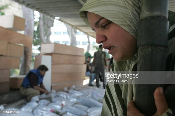 Lebanese woman views the bodies of victims of the Israeli air strike in Qana are seen at the morgue wrapped in plastic after being brought from Qana...
