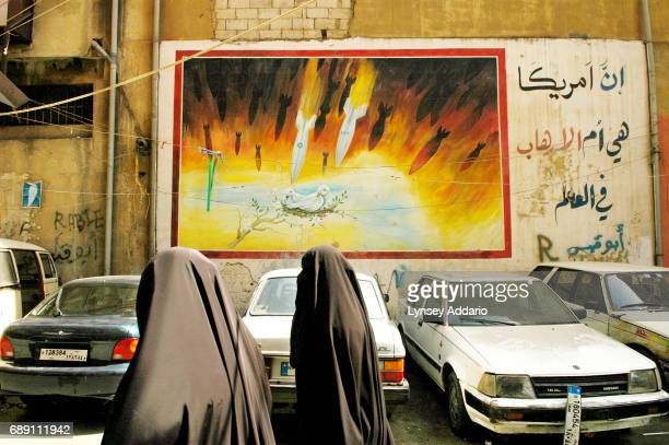 Lebanese woman waslks past an anti-American and Israeli mural in Beirut's southern suburbs, in Lebanon, September 19, 2006. As more and more United...