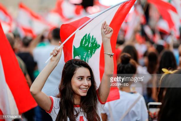 A Lebanese woman waves a national flag during a rally on the sixth day of demonstrations against tax increases and official corruption in Zouk Mosbeh...