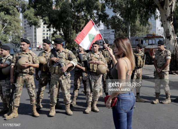 A Lebanese woman waves a national flag in front of soldiers standing guard on a main road in the eastern outskirts of the capital Beirut on October...