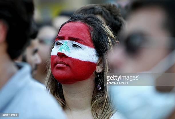 A Lebanese woman with her face painted in the colours of Lebanon's national flag takes part in a demonstration in downtown Beirut on August 8 against...