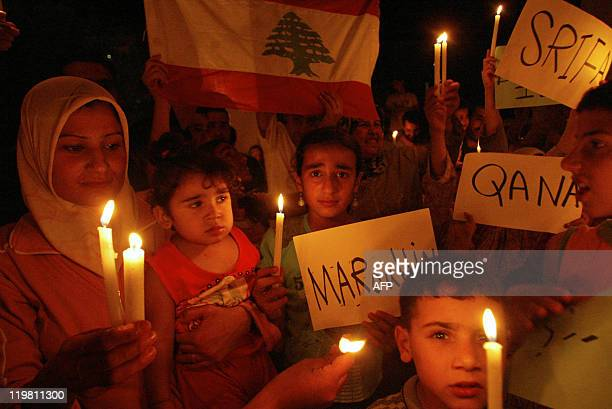 Lebanese women and children displaced from southern Lebanese villages hold candles and signs reading the names of Lebanese villages Qana Srifa and...