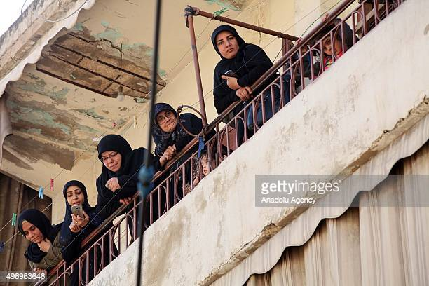 Lebanese women are seen on a balcony as soldiers inspect an area where two explosions took place at Dahieh, know as Hezbollah stronghold, South...