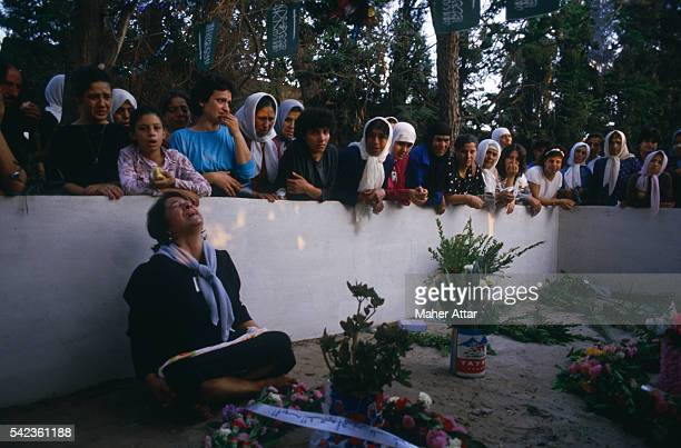 Lebanese women crying over the graves of their children who died during the war
