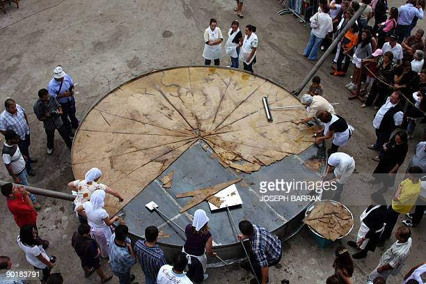 Lebanese women cut the biggest kibbeh dish a middle eastern specialty made of bulgur and spiced minced meat after entering the Guinness World Records...