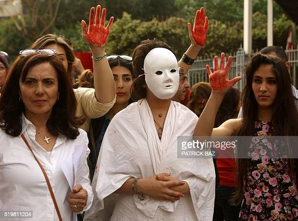 Lebanese women flash the palm of their hands colored in red as they demonstrate against prostitution sex slavery and violence against women in front...