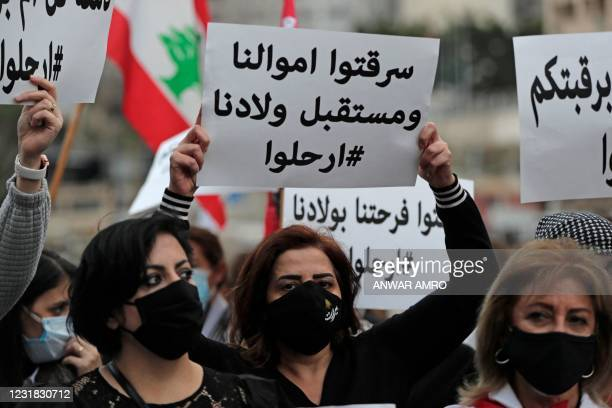 Lebanese women hold placards as they protest against the country's political paralysis and deep economic crisis in Beirut on the occasion of Mother's...