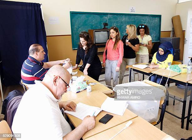 Lebanese women stand in line to cast their votes for the municipal elections at a polling station on May 8 2016 in the capital Beirut Lebanese headed...