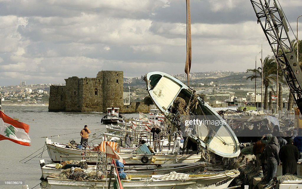 Lebanese workers pull a fishing boat from the sea at the port of Sidon in southern Lebanon after it was damaged in a storm on January 10, 2013. A severe snow and rain storm that has been battering Lebanon since the weekend is one of the worst to have hit the country in at least a decade, an airport weather expert has said.