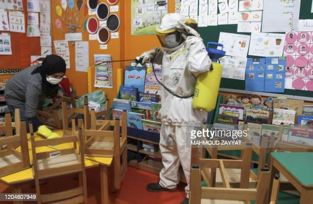 Lebanese workers spray disinfectant in classrooms and halls of a school in the coastal town of Rmeileh, 35 Kms south of the capital Beirut, on March...