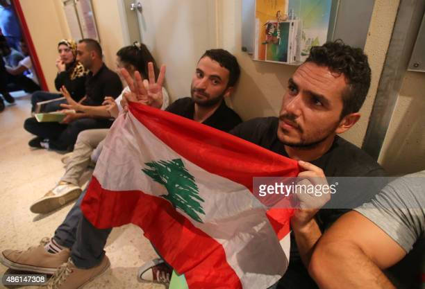 A Lebanese young man holds a national flag flashing the sign of victory among fellow activists sitting in a hallway during a surprise sitin at...