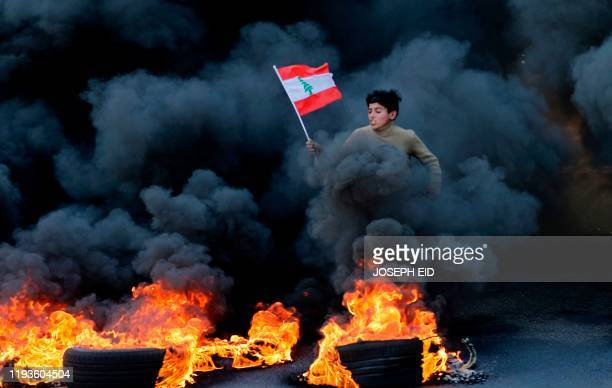 Lebanese youth runs with a national flag as smoke billows from burning tires during a demonstration in Jal el-Dib area on the northern outskirts of...