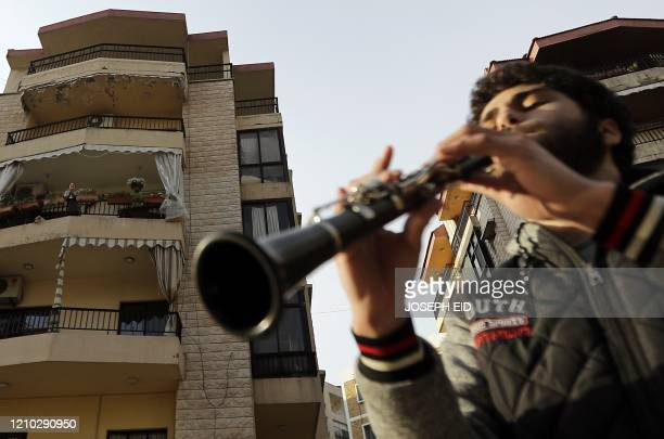 Lebanese youth Yamen alMokhtar plays his clarinet in the neighbourhoods of Aley city east of the capital Beirut to entertain confined residents amid...