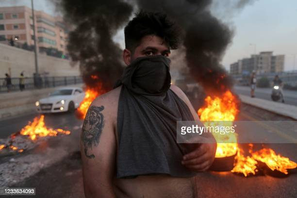 Lebanese youths burn tires to block a main highway in the area of Jal el-Dib, east of the capital Beirut, as they protest against the country's dire...