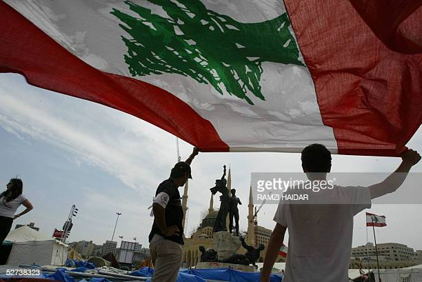Lebanese youths fold their national flag as the Lebanese opposition started dismantling its tents on Martyrs Square in Beirut's downtown 30 April...