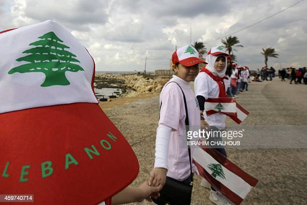 Lebanese youths form a human chain as they take part in an event organised by the NGO Beirut Celebrations on November 30 2014 in the northern city of...