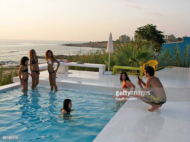 Lebanese youths hang around the swimming pool at sunset in Lazy Bee beach resort on the outskirts of Beirut towards Sidon on August 17 2008 After the...