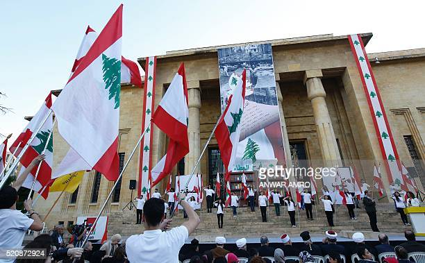 Lebanese youths hold national flags during a rally organised by the Joy of Giving NGO to mark the 41st anniversary of the civil war in Lebanon on...