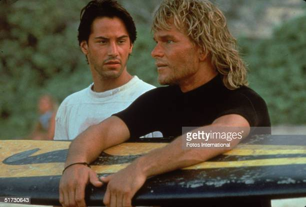 Lebaneseborn American actor Keanu Reeves and American actor Patrick Swayze stand on a beach as Swayze holds a surfboard during the filming of the...
