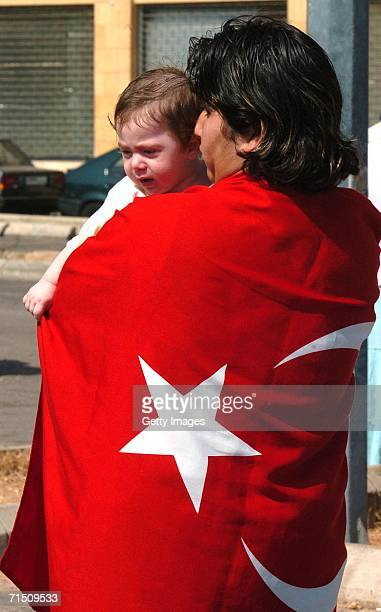 A LebaneseTurkish man draped by a Turkish flag holds his child and waits to be evacuated July 24 2006 in Beirut Lebanon Turkish Special Forces escort...