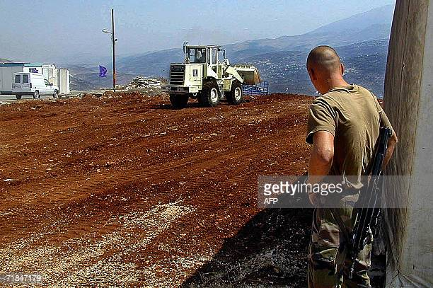 A French soldier from the Legion Etranger looks at a UN caterpillar working on paving a piece of land to erect a camp for French troops in the...