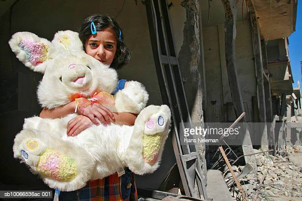 Lebanon, Aitachab, Girl standing with stuffed animal in front destroyed house, close-up, portrait