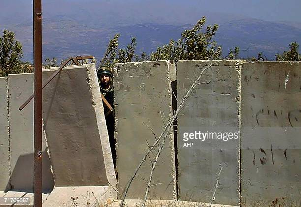 An Israeli soldier looks from behnid concrete blocks located at the Israeli side of the Blue Line that separtes the Jewish country from Lebanon at...