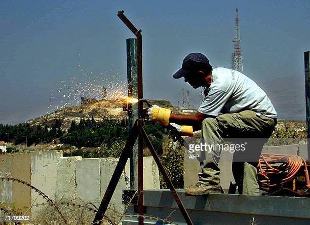 An Israeli worker fixiex a barbed wire at the Israeli side of the Blue Line that separtes the Jewish country from Lebanon at the area of Kafar kila...