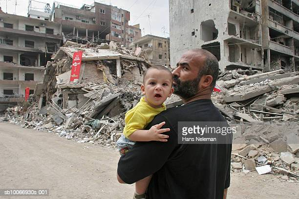 Lebanon, Beirut, Father with son (21-24 months) walking through ruins of city destroyed by war