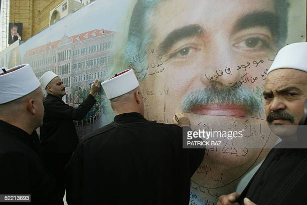 Druze Lebanese clerics sign their names in a show of support and grief 18 February 2005 on a huge mural portrait of Lebanon's assassinated former...