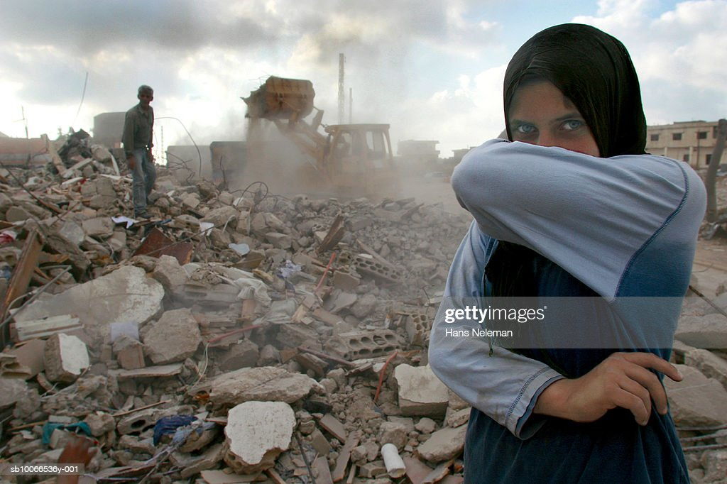 Lebanon, Sidiken, Girl in destroyed town covering mouth from ashes, portrait : Stock Photo