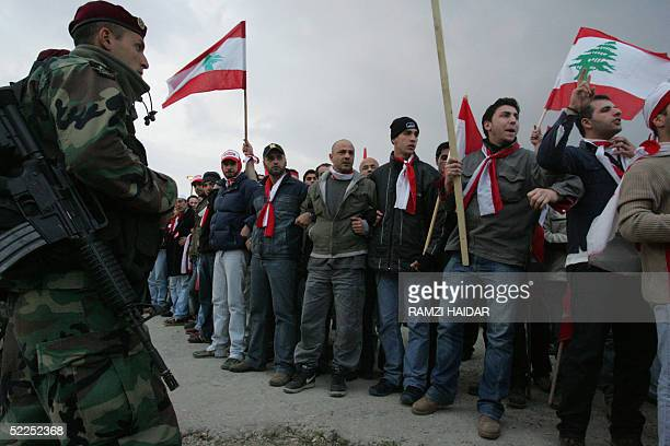 Thousands of demonstrators waving national flags and shouting antiSyria slogans face Lebanese marine commando forces as they prepare to break through...