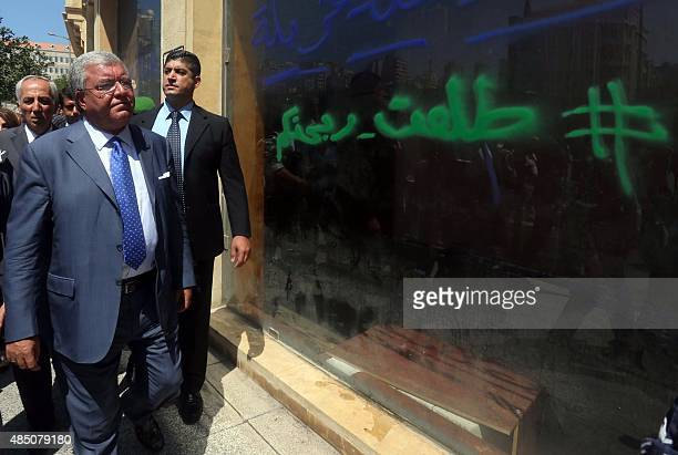 Lebanons interior minister Nuhad alMashnouq looks at a shop painted with graffiti in downtown Beirut on August 24 2015 during a visit to inspect the...
