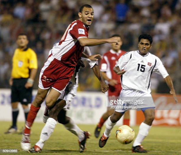 Lebanon's Roda Antar is tackled by Luthfy Ashraf of Maldives during their 2006 World Cup Asian zone qualifying match in Beirut 09 June 2004 AFP PHOTO...
