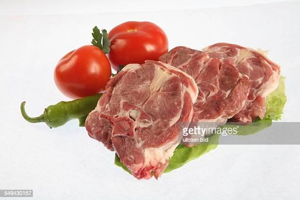 Lebensmittel Fleisch Rohes Nackenkotelett auf Salat mit Tomaten und Peperoni
