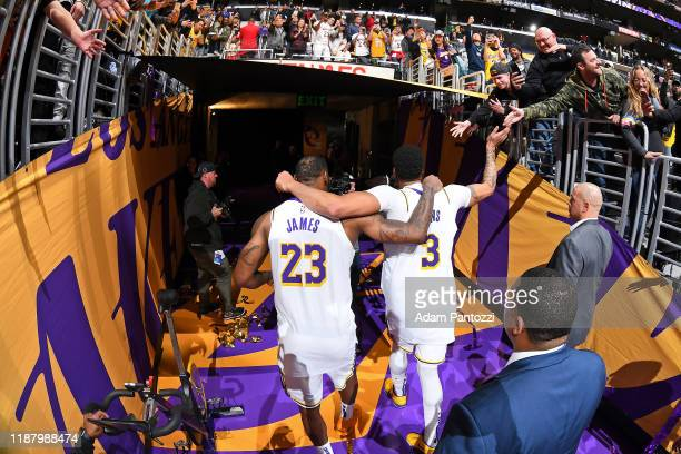 LeBron James and Anthony Davis of the Los Angeles Lakers interact with fans as they walk off the court after the game against the Minnesota...
