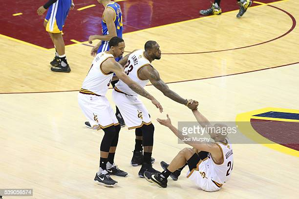 LeBron James and Channing Frye help up teammate Richard Jefferson of the Cleveland Cavaliers during the game against the Golden State Warriors in...