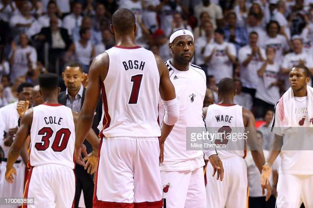 LeBron James and Chris Bosh of the Miami Heat celebrate in the second half during a timeout against the San Antonio Spurs during Game One of the 2013...