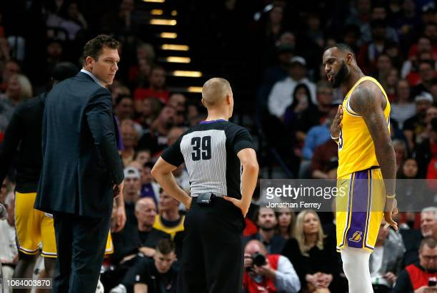 Lebron James and Head Coach Luke Walton of the Los Angeles Lakers speak to a referee during the game against the Portland Trail Blazers at Moda...
