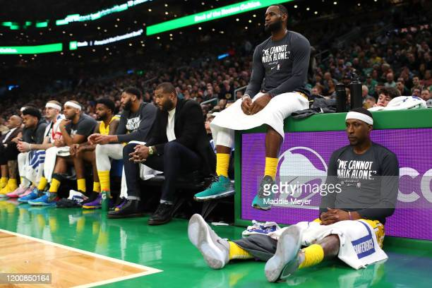 LeBron James and Kentavious CaldwellPope of the Los Angeles Lakers look on from the bench during the game against the Boston Celtics at TD Garden on...
